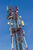 Red and white antenna over blue sky poster