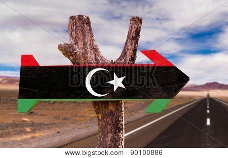 Libya Flag wooden sign with desert road background