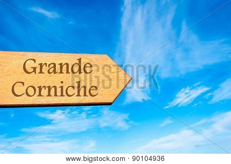 Wooden arrow sign pointing destination Grande Corniche FRANCE against clear blue sky with copy space available. Travel destination conceptual image poster