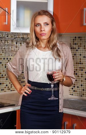 thoughtful woman with a glass of red wine in kitchen