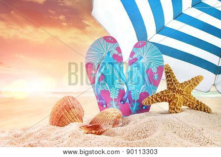 Pair of flip-flops in the sand with starfish at sunset