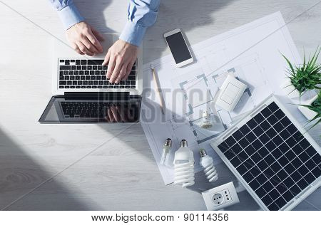 Man working at his desk on a laptop with energy saving CFL lamps a solar panel and a house project top view poster