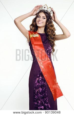 fashion studio photo of beautiful gorgeous young woman with luxurious hair wearing elegant dress and victress crown and ribbon of beauty contest poster