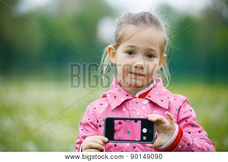Little Girl Holding A Smart Phone With Picture On Display