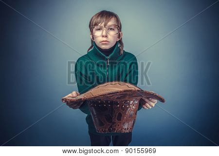 European-looking boy of ten years in  glasses holding  a hat, a