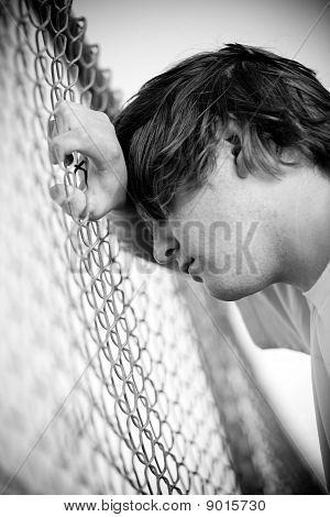 Depressed Teen Against Fence