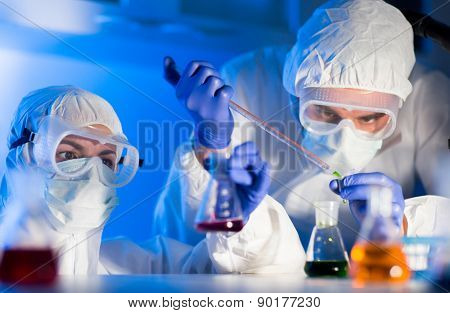 science, chemistry, biology, medicine and people concept - close up of young scientists with pipette and flasks making test or research in clinical laboratory