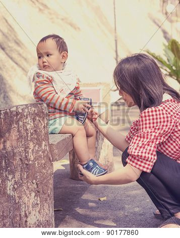 Mother wearing shoe to baby