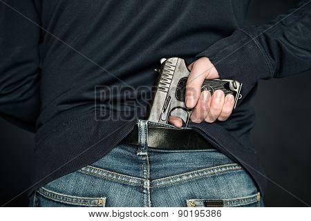 A Person Is Hiding A Handgun Under The Denim Belt.