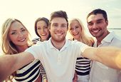 summer, sea, tourism, technology and people concept - group of smiling friends with camera on beach photographing and taking selfie poster