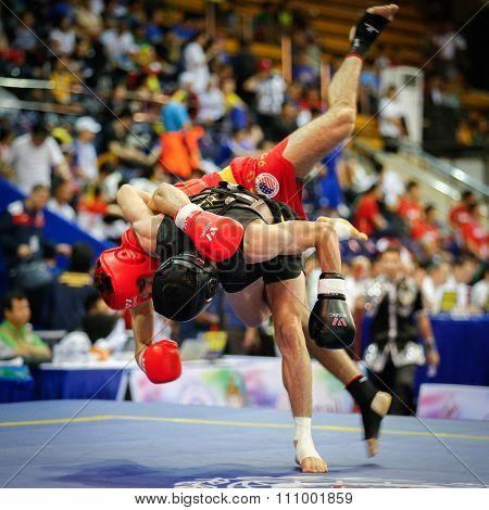 JAKARTA, INDONESIA - NOVEMBER 15, 2015: Jafar Topraghlou of Iran (black) throws Jorge Cortez of USA (red) in the men's 65kg Sanda event at the 13th World Wushu Championship 2015 in Istora Senayan.