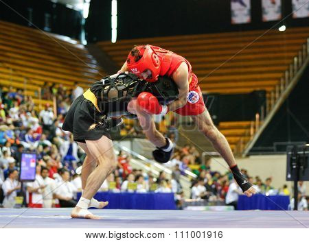 JAKARTA, INDONESIA - NOVEMBER 15, 2015: Jafar Topraghlou of Iran (black) fights Jorge Cortez of USA (red) in the men's 65kg Sanda event at the 13th World Wushu Championship 2015 in Istora Senayan.
