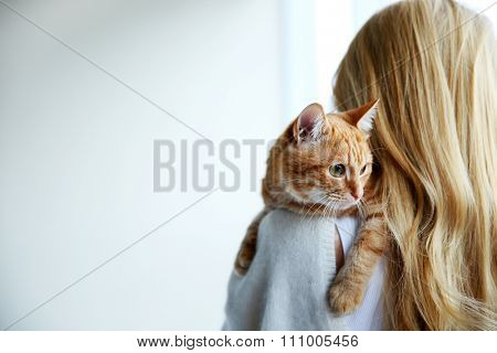 Young woman holds red cat in hands, close up, back view