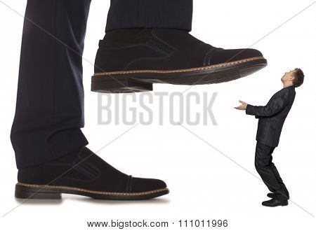 Cared small businessman under big leg his boss, isolated on white background