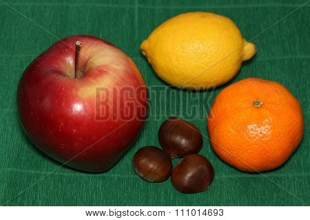 Apple,lemon,Mandarin and three chestnuts on green background