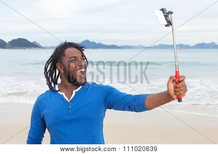 African American Guy With Dreadlocks At Beach Taking Picture With Selfie Stick