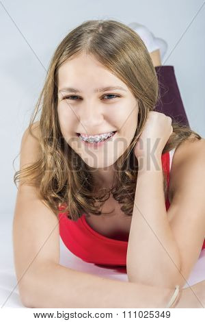 Positively Looking Young Caucasian Female With Teeth Bracket System. Against White Background