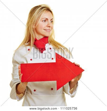 Young female cook in workwear holding a big red arrow