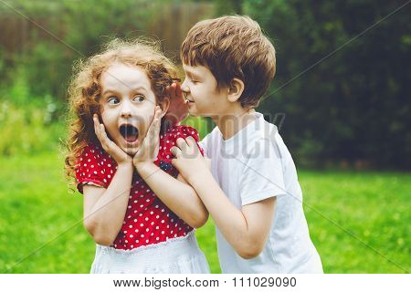 Surprised Little Girl And Boy Talking With Whispers.