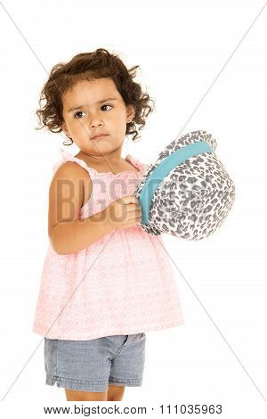 Hispanic Toddler Girl Holding A Leopard Print Hat Glancing Sidewards