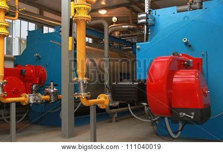 Blue boilers and red gas burners in a modern boiler-house