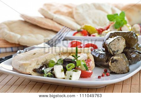Cold Greek appetizers: stuffed flat bread, stuffed vine leaves, sheep's milk cheese, olives, tzatziki poster