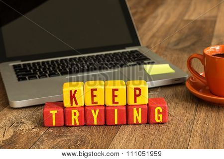 Keep Trying written on a wooden cube in a office desk