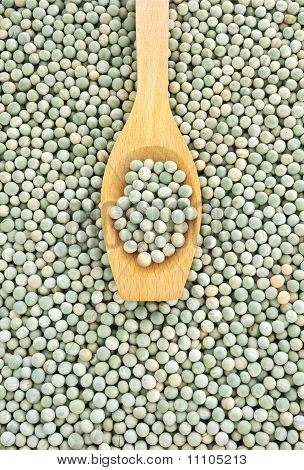 Wooden spoon and dried green split peas