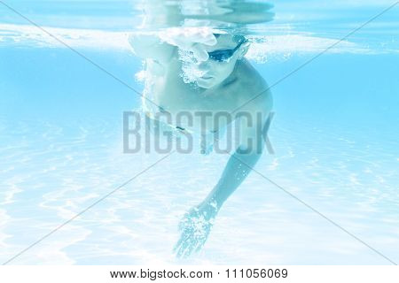 young man swimming the front crawl style in a pool