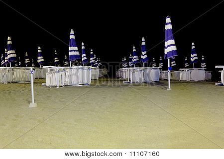 Many Lounges And Closed Umbrellas On Night Beach, Black Sky