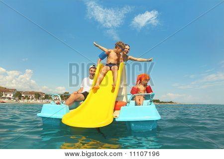 Family With Boy And Girl On Pedal Boat With Yellow Slide In Sea, View From Water