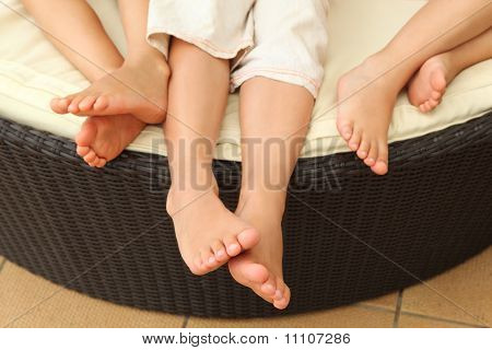 Legs Of Three Barefooted Children Lying On Circle Sofa