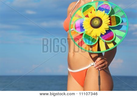 Closeup Of Woman In Orange Bikini Standing On Beach And Holding Pinwheel Toy, Sea And Sky
