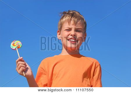 Little Boy In Orange Shirt Holding Multicolored Lollipop, Blue Sky