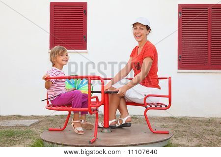 Mother And Daughter Sitting On Merry-go-round At Playground And Smiling, White Building