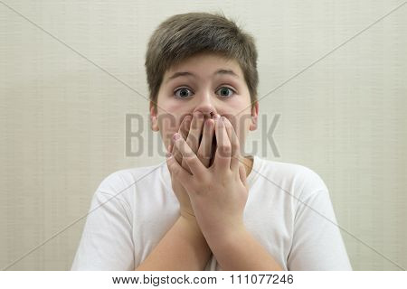 Surprised boy closes the mouth with  hands