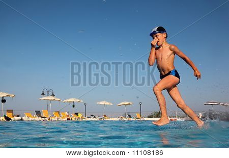 Little Boy With Glasses For Swimming Dives Into Blue, Clear Water Of Pool.