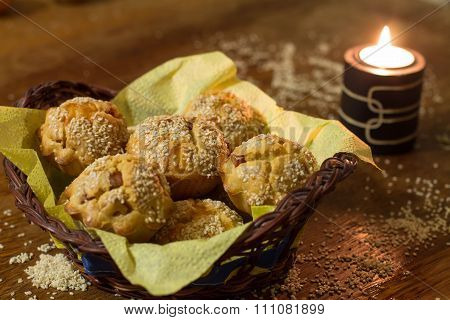 Salty muffins with sausage, cheese and sesame in wood basket
