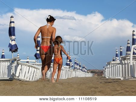 Young Mother And  Little Daughter In Bathing Suit Going On Beach. Mother Holds Daughter's Hand