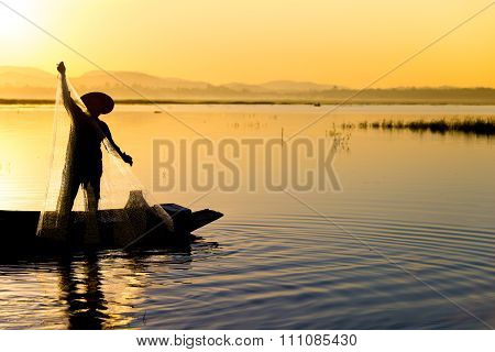 Silhouette Fisherman in action fishing, sihouette portrait.