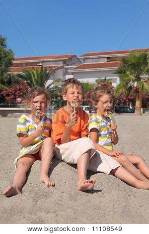 Little Boy And Two Girls Sitting On Beach And Eating Multicolored Lollipops, Palms And Building