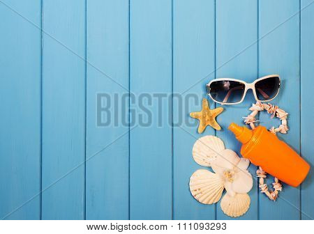 Shells, sunblock and sunglasses on blue board