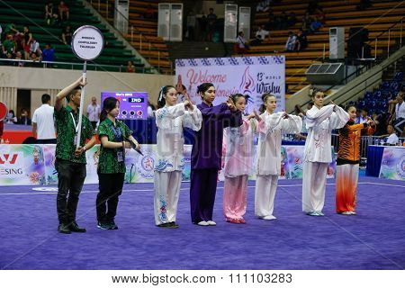 JAKARTA, INDONESIA - NOVEMBER 16, 2015: Athletes take to the arena to commence the Women's Compulsory Taijiquan event at the 13th World Wushu Championship 2015 at the Istora Senayan Stadium.