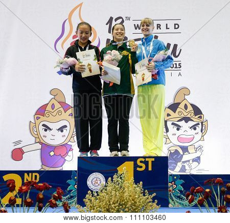 JAKARTA, INDONESIA - NOVEMBER 16, 2015: Winners take to the podium at awards ceremony for the women's Compulsory Nanquan event at the 13th World Wushu Championship 2015 at the Istora Senayan Stadium.