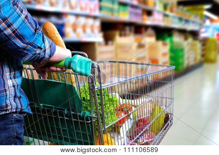 Man Pushing Shopping Cart In The Supermarket Aisle