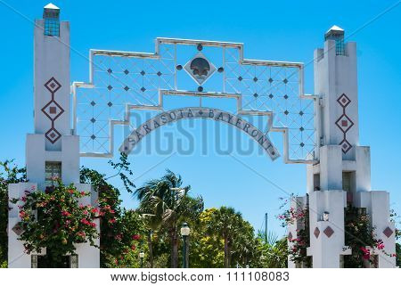 SARASOTA, FLORIDA - JUNE 13, 2013: Bayfront Park for leisure activities.  Entrance portal of tourist attraction opened in 1992 that has red flowers and surrounded by tropical foliage and trees