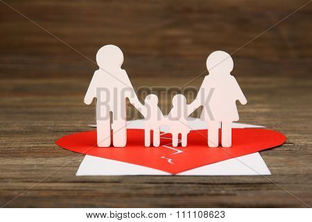 Cutout silhouette of a family split apart on a paper heart, divorce concept poster