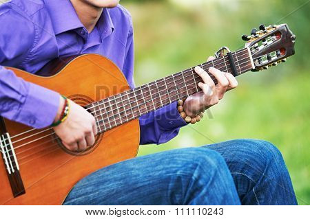 Close up of guitarist hands playing music chords on acoustic six string guitar outdoors