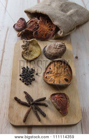 Healthy herbs table (dried long pepper,bare fruit,mushroom,black pepper) on wooden background.