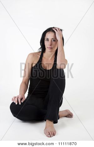 Woman in exercise clothes, sitting on the floor